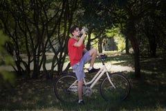 El hombre joven se sienta en la bici en el agua de reclinación de madera de la bebida fotos de archivo libres de regalías