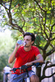 El hombre joven se sienta en la bici en el agua de reclinación de madera de la bebida imágenes de archivo libres de regalías