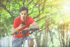 El hombre joven se sienta en la bici en el mensaje que manda un SMS de madera en smartphone fotos de archivo