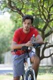 El hombre joven se sienta en la bici en la botella de reclinación de madera del control de agua fotografía de archivo