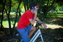 El hombre joven se sienta en la bici en la charla de reclinación de madera sobre smartphone imagen de archivo libre de regalías