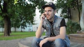 El hombre joven se sienta en superficie del granito y hablar en el teléfono Árbol en campo gladness metrajes