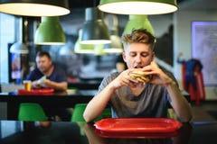 El hombre joven se sienta en un restaurante y miradas cuidadosamente en la hamburguesa que se sostiene en sus manos Fotos de archivo libres de regalías