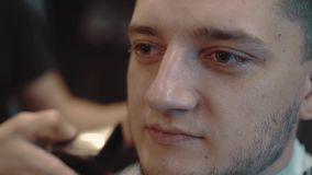 El hombre joven se sienta en una peluquería de caballeros, él se compone con una barba, primer, cámara lenta almacen de video