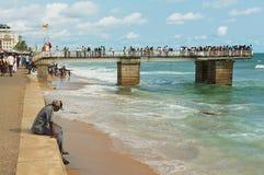 El hombre joven se sienta solamente en la playa en Colombo, Sri Lanka Imagenes de archivo
