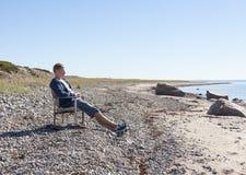 El hombre joven se sienta y se relaja en silla en la playa Fotos de archivo libres de regalías