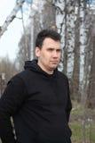 El hombre joven se vistió en soportes negros en bosque de la primavera Imagen de archivo libre de regalías