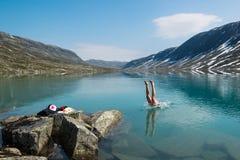 El hombre joven se zambulle en un lago frío de la montaña, Noruega Foto de archivo