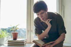 El hombre joven serio concentrado leyó el libro Fotos de archivo libres de regalías