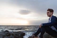 El hombre joven serio en traje elegante se sienta en la costa cerca del océano Imagen de archivo libre de regalías