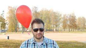 El hombre joven serio y brutal en vidrios negros se coloca con un globo rojo y las miradas en la cámara, sorpresa, lento-MES metrajes