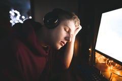 El hombre joven soñoliento goza de un ordenador en la noche El videojugador bajó dormido mientras que jugaba en un ordenador foto de archivo