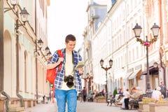 El hombre joven sonriente con la cámara y la ciudad trazan Imagenes de archivo