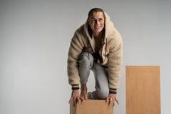 El hombre joven sonriente elegante en sportwear se agachó en el cubo de madera y la presentación foto de archivo libre de regalías