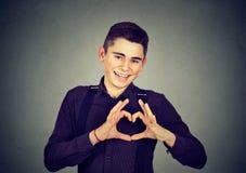 El hombre joven sonriente hermoso hace forma del corazón con las manos de los fingeres Fotos de archivo libres de regalías