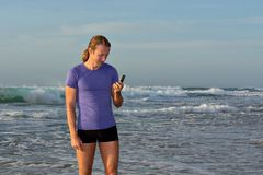 El hombre joven sonriente lee sms en la playa foto de archivo