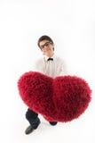 El hombre joven sonriente lleva a cabo un corazón rojo Imagen de archivo
