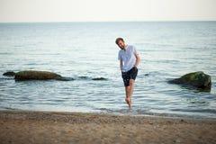 El hombre joven sonriente salpica el agua en la playa Foto de archivo