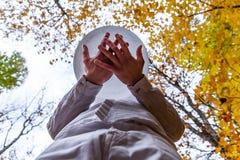 El hombre joven sostiene su cuenco cristalino solemnemente en el bosque - de debajo 2/2 foto de archivo