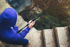El hombre joven sostiene una caña de pescar y coge los pescados en la naturaleza en un fondo del mar, inconformista que el pescad Imagen de archivo libre de regalías