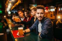 El hombre joven sostiene el vidrio con la cerveza en el contador de la barra Imagenes de archivo