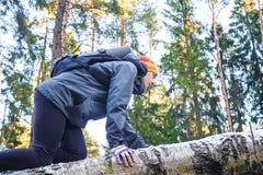 El hombre joven sube sobre un abedul caido en el bosque Imágenes de archivo libres de regalías