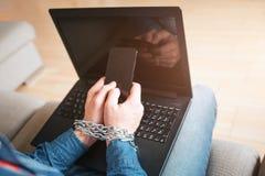 El hombre joven tiene apego social de los medios Addictivenes del ordenador portátil o del smartphone Sostener el tel?fono en man fotos de archivo