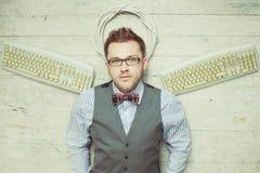 El hombre joven tiene gusto de un ángel con los teclados Foto de archivo libre de regalías