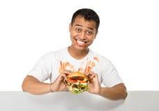 El hombre joven tiene un gran deseo de comer una hamburguesa Fotos de archivo