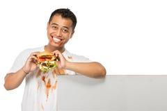 El hombre joven tiene un gran deseo de comer una hamburguesa Fotografía de archivo