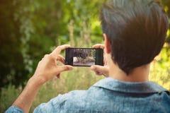 El hombre joven toma la foto con el smartphone al aire libre foto de archivo