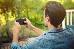 El hombre joven toma la foto con el smartphone al aire libre foto de archivo libre de regalías