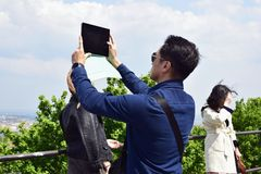 El hombre joven toma una imagen con una tableta de una vista pintoresca de la ciudad imagen de archivo