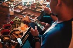 El hombre joven toma una imagen de su comida para la red social Concepto del apego de Internet Los amigos desayunan en café imagenes de archivo