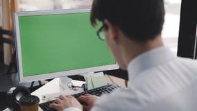 El hombre joven trabaja con PC con la pantalla y el teclado verdes 4K