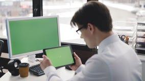 El hombre joven trabaja con PC y la tableta con la pantalla verde 4K almacen de metraje de vídeo