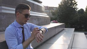 El hombre joven trabaja con su smartwatch almacen de video