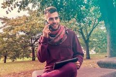 El hombre joven trabaja en la tableta mientras que habla en el teléfono al aire libre en espacio público cerca de parque imagen de archivo