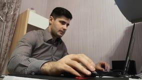 El hombre joven trabaja en su ordenador portátil para conseguir todo su negocio hecho temprano por la mañana almacen de video