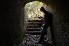 El hombre joven trabaja en un Smart-teléfono en túnel oscuro Imágenes de archivo libres de regalías