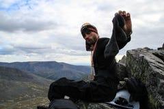 El hombre joven turístico cambia calcetines stinky viejos durante un alza imagen de archivo