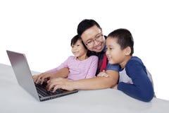 El hombre joven utiliza el ordenador portátil con sus niños foto de archivo