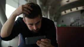 El hombre joven utiliza smartphone para comprobar su corte de pelo en el aeropuerto almacen de metraje de vídeo