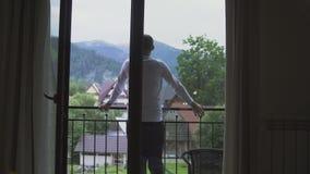 El hombre joven va de su sitio al balcón, mirada en las montañas metrajes