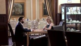 El hombre joven vestido, confiado respetable con una barba toca la mano de la mujer rubia en el vestido de noche El sentarse en e almacen de metraje de vídeo