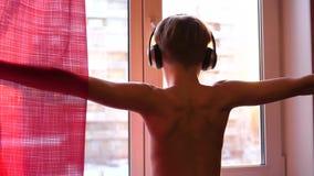 El hombre joven viene a la ventana, lleva los auriculares para escuchar la música Fondo borroso con la puesta del sol, goce adole almacen de video