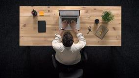 El hombre joven viene y trabaja en el ordenador portátil en el d3ia, concepto del trabajo, concepto de la oficina, concepto de la almacen de video