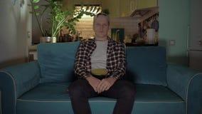 El hombre joven vino y se sentó rápidamente en un sofá azul en el fondo de la cocina 4K almacen de metraje de vídeo
