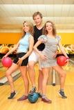 El hombre joven y dos muchachas sostienen bolas en club del bowling Foto de archivo libre de regalías