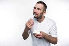 El hombre joven y fuerte está comiendo el yogur Él está haciendo eso con placer Aislado en el fondo blanco fotos de archivo